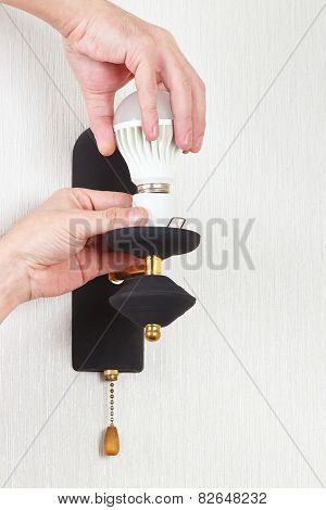 Hand replace led bulb in the a lamp on white wall