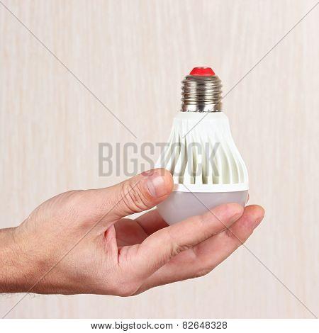 Hand holding a light bulb on light wood background