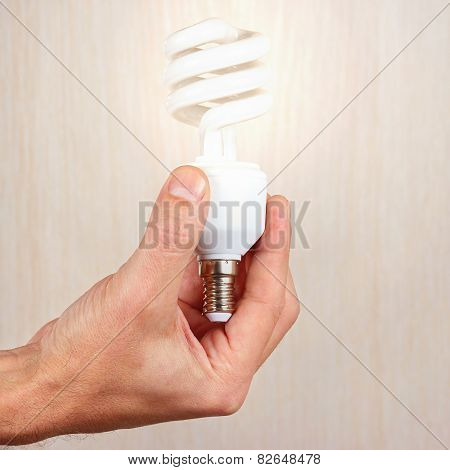 Hand holding a glowing tungsten bulb on light wood background
