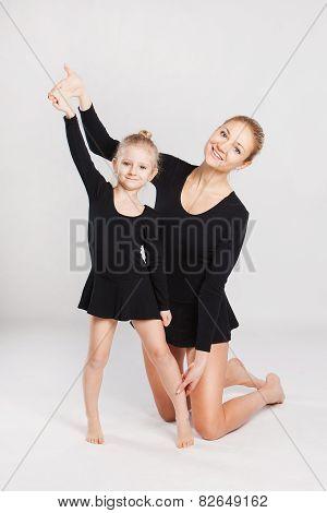Mom teaching gymnastics daughter.
