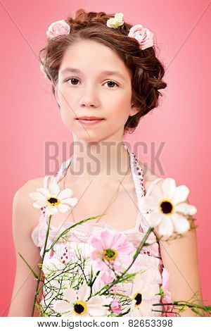 Portrait of a beautiful girl with braided hair wearing summer sundress. Children fashion.