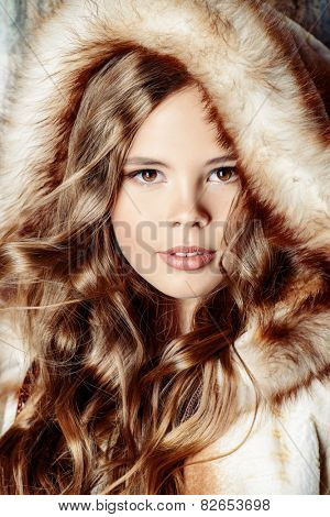 Fashion shot of a pretty teenager girl with beautiful long curly hair wearing fur coat. Beauty, fashion.