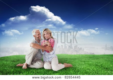 Happy couple sitting and holding heart pillow against blue sky over city