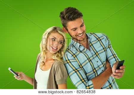 Attractive couple using their smartphones against green vignette