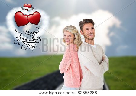 Attractive couple smiling with arms crossed against road on grass