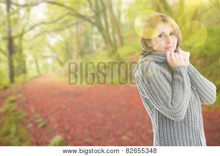 Pretty girl in jumper against peaceful autumn scene in forest