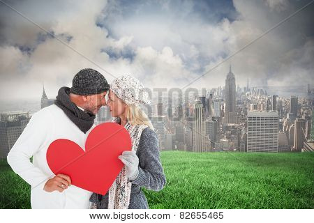 Smiling couple in winter fashion posing with heart shape against cloudy sky over city