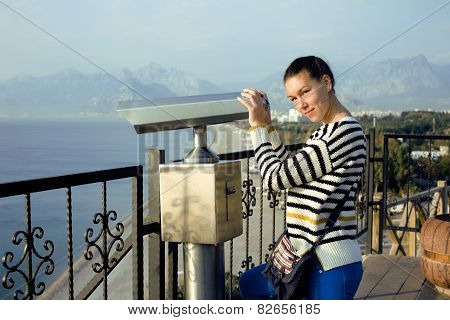 young woman looking through telescope at sea viewpoint in Atatur
