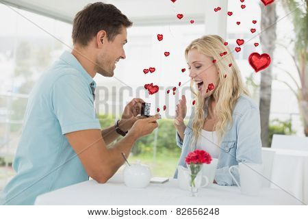 Man proposing marriage to his shocked blonde girlfriend against red heart balloons floating