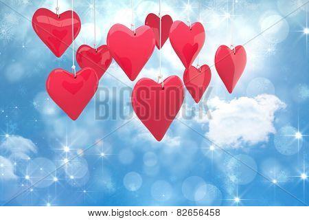 Love hearts against shimmering light design on blue