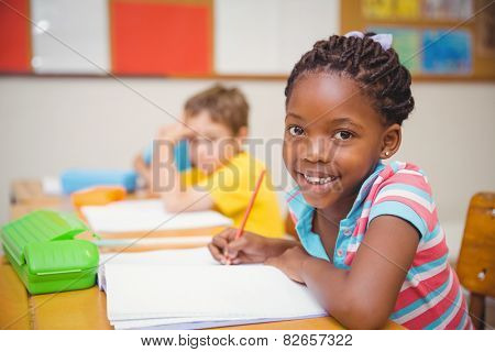 Cute pupils drawing at their desks one smiling at camera at the elementary school