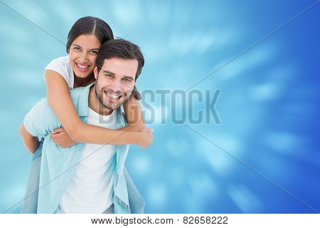 Happy casual man giving pretty girlfriend piggy back against valentines heart design