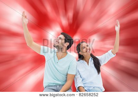 Cute couple sitting with arms raised against digitally generated twinkling light design