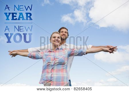 Happy couple standing outside with arms stretched against new year new you