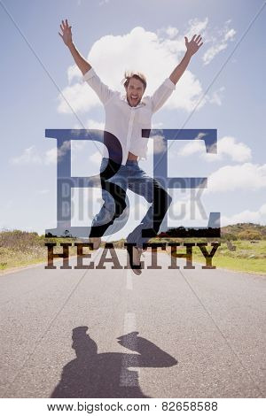 Handsome casual man leaping on a road smiling at camera against be healthy
