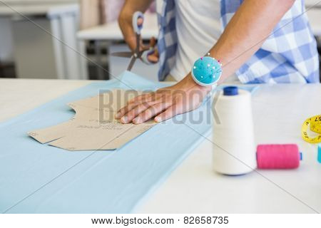 Fashion student cutting fabric with pair of scissors at the college