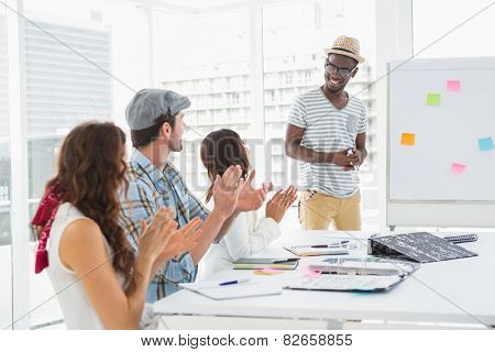 Smiling colleagues sitting and applauding businessman in the office
