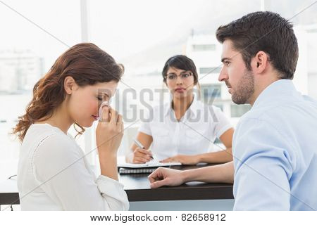 Troubled couple talking with their therapist in the office