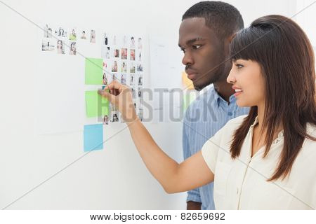 Teamwork standing and taking sticky notes in the office