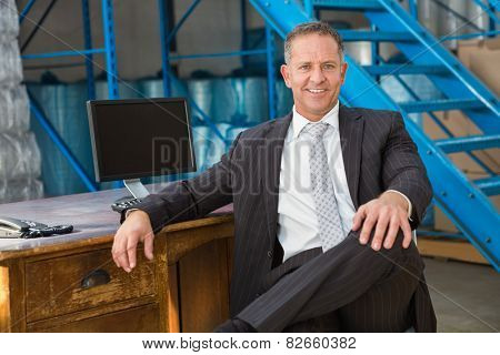 Smiling warehouse manage sitting with his legs crossed in a large warehouse