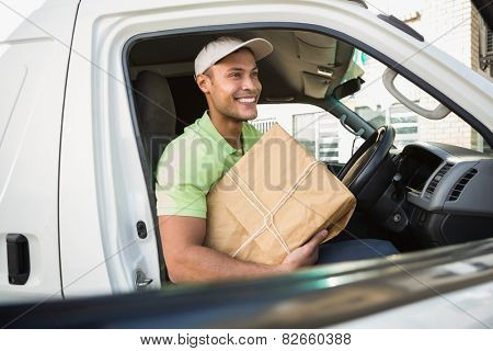 Smiling delivery driver in his van holding parcel outside warehouse