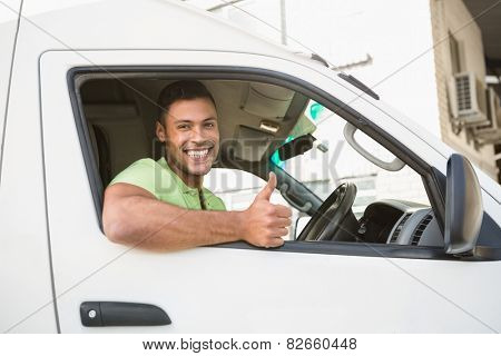 Smiling man showing thumbs up driving his van outside the warehouse