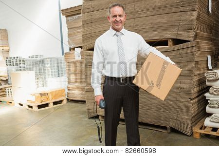 Warehouse manager holding cardboard box and scanner in a large warehouse