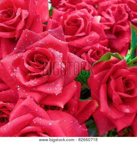 wet fake red roses closeup