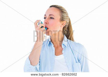 Pretty blonde using an asthma inhaler on white bakcground