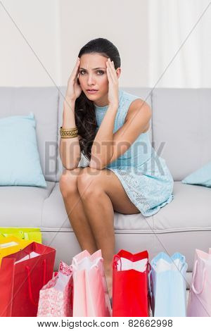Regretful brunette with many shopping bags at home in the living room