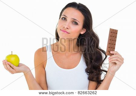 Pretty brunette deciding between apple and chocolate on white background