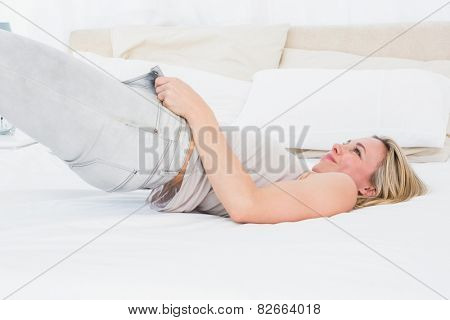 Focused blonde forcing to close her jeans on the bed in hotel room