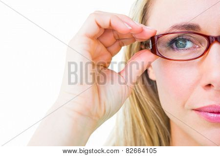 Close up of pretty blonde with red reading glasses on white background