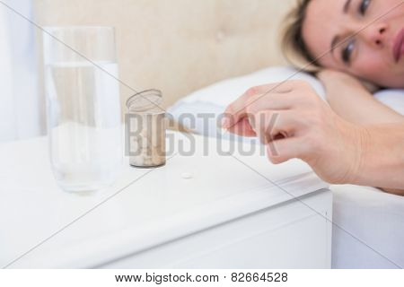 Pretty blonde lying bed taking pills on bedside table at home in the bedroom