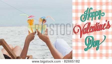 Couple clinking glasses of cocktail on beach against happy valentines day