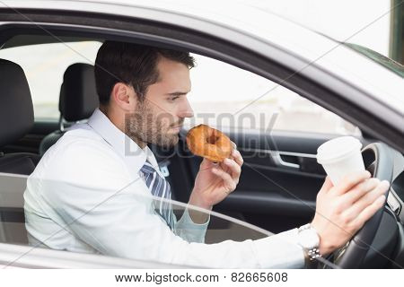 Young businessman having coffee and doughnut in his car