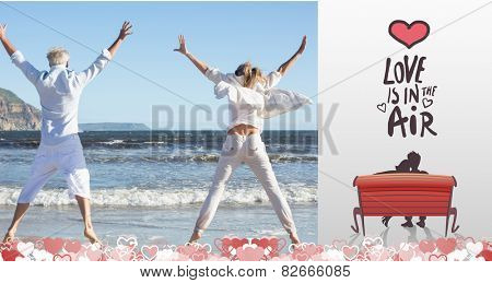 Couple jumping on the beach together against love is in the air