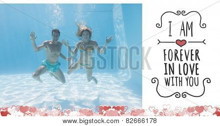 Cute couple smiling at camera underwater in the swimming pool against valentines message