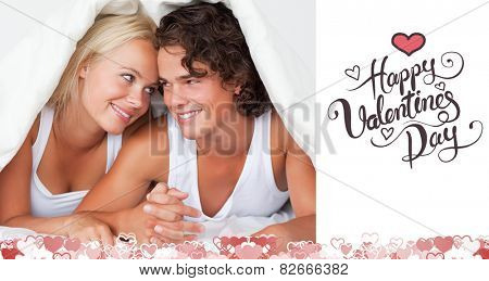Portrait of an in love couple under a duvet against happy valentines day