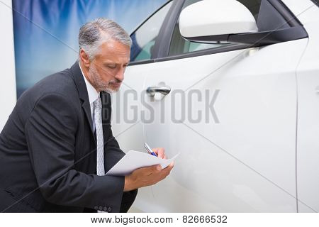 Businessman looking at car while writing on clipboard at new car showroom