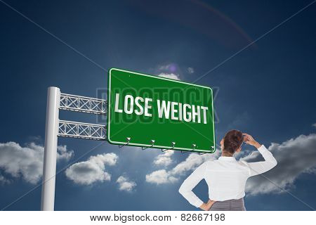 The word lose weight and businesswoman scratching her head against sky