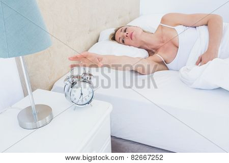 Blonde woman lying in bed reaching for alarm clock at home in the bedroom