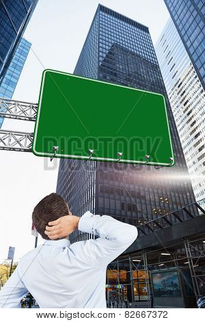 Thinking businessman scratching head against skyscraper in city