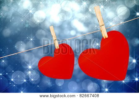 Hearts hanging on a line against shimmering light design on blue