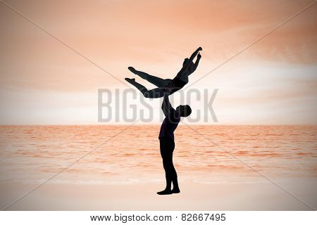 Ballet partners dancing gracefully together against beach scene