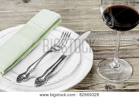 A white plate, a fork, a knife, a green napkin dining room and  a wine glass on a wooden background
