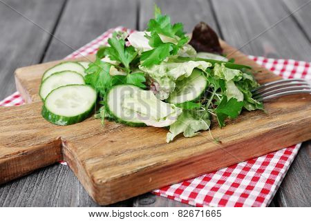 Sliced cucumber and greens on cutting board and wooden planks background