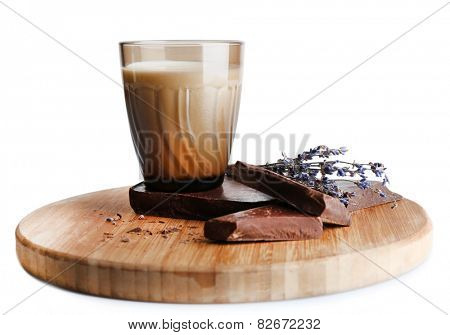 Glass of milk with chocolate chunks and dried flower on wooden cutting board isolated on white