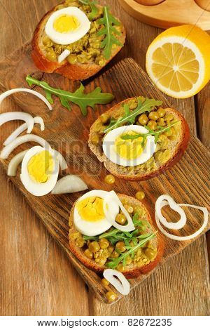 Sandwiches with green peas paste and boiled egg with onion rings and lemon on wooden planks background