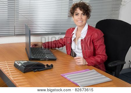A Smiling Business Woman In Red, Sitting Satisfied At Desk